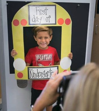 Child Posing with a School Bus Frame on the First Day of Kindergarten