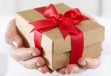 hands holding a brown box with a red bow tied around it