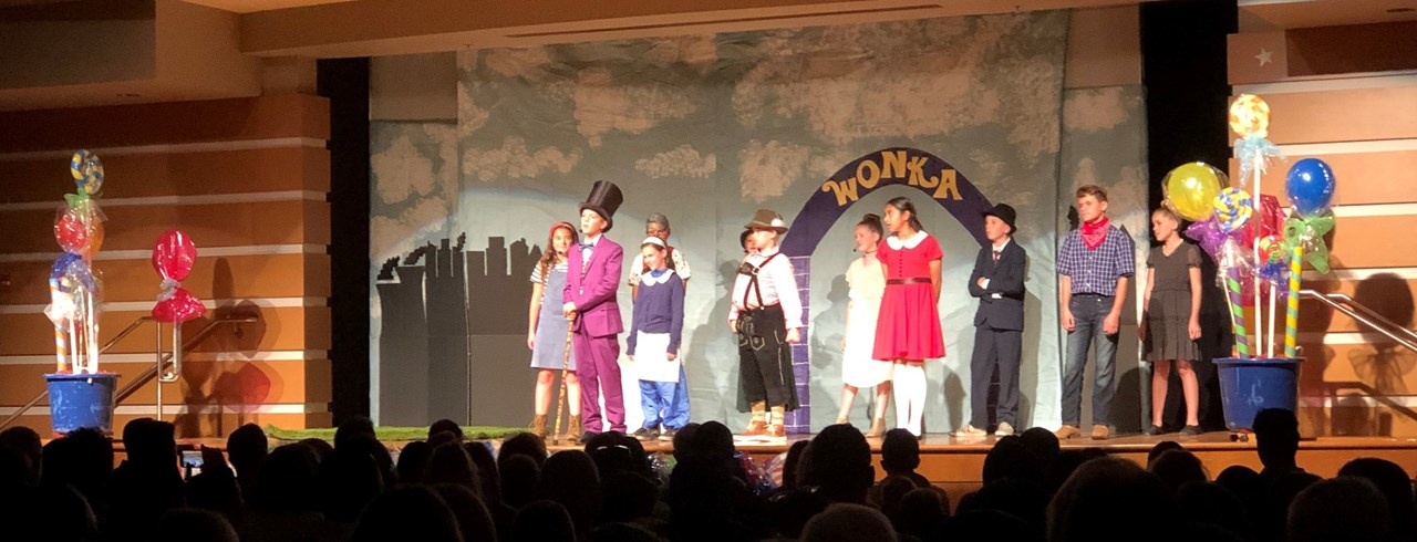 Photo of students performing in school production of Willy Wonka Kids.